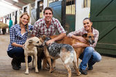 Group of farm workers with dogs — Stock Photo