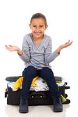 Girl sitting on overfilled suitcase — Stock Photo