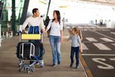 Family with suitcases at airport — Stock Photo
