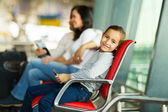 Lovely little girl holding tablet pc at airport — Stock Photo