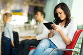 Woman using tablet at airport — Stock Photo