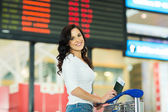 Woman near airport information board — Stock Photo