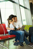 Family using laptop at airport — Stock Photo