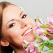 Beautiful happy young woman holding pink spring flowers — Stock Photo