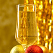 One glass of champagne with a Christmas decor in the background. — Stock Photo