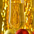 Stock Photo: one glass of champagne with a christmas decor in the background