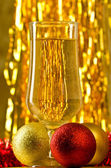 One glass of champagne with a Christmas decor in the background — Stock Photo