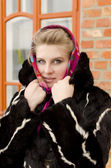 Girl is bundled up against the cold in a fur coat — Stock Photo