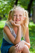 Sweet, playful blond girl sitting in the green garden and backin — Stock Photo