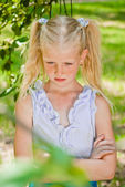 Blonde girl standing in a garden with hands clasped, looking at — Stock Photo