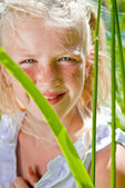 Freckled girl looks out from behind the leaves — Stock Photo
