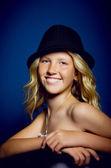 Vacker flicka sitter på en stol med en hatt — Stockfoto