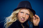 Girl smiling holding on to the hat and looking at the camera — Stock Photo