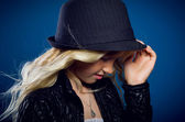 Sad girl keeps for his hat and looking down — Stock Photo