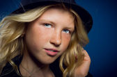 A girl holds up his hat and looking at the camera — Stock Photo