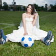 Bride in white dress on a soccer field. — Stock Photo