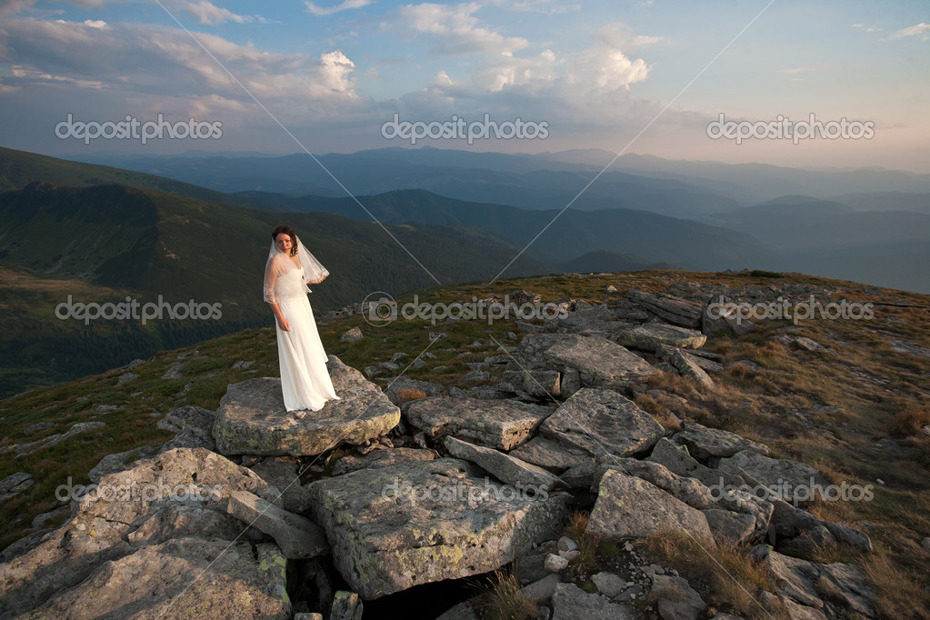Bride in wedding dress standing high in mountains. — Stock Photo #18370547