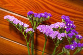 Purple flowers on a decorative wood background — Stock Photo