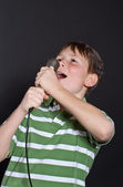 Teen singing into a microphone — Stock Photo