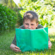 Boy with a book on the grass — Stock Photo