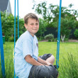 Teenager sitting on a swing — Stock Photo #25988569