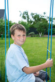 Teenager sitting on a swing — Stock Photo
