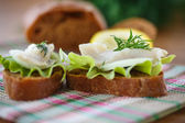Sandwich salted herring and lettuce — Stock Photo