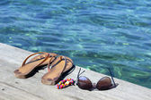 Flip-flop, sunglasses and  bracelets — Stock Photo