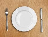 Placa blanca redonda, cuchillo y tenedor de mesa de madera — Foto de Stock