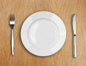 Round white plate, knife and fork on wooden table — Stock fotografie
