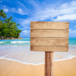 Wooden signboard on tropical beach — Stock Photo #12584979