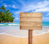 Wooden signboard on tropical beach — Stok fotoğraf