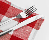 Knife and fork on red checked tablecloth — Stock Photo
