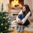 Happy teenage girl in winter clothes sitting fireside — Stock Photo #12831407