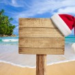 Tropical beach wooden signboard with Christmas hat — Stock Photo