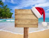 Letrero de madera tropical playa con sombrero de la navidad — Foto de Stock