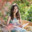 Girl reading book sitting in wicker chair outdoor in summer day — Stock Photo