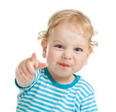 Funny curly child with dirty lips pointing by finger directly to — ストック写真