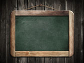 Aged green blackboard hanging on wooden wall as a background for — Stock Photo