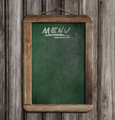 Aged green menu blackboard hanging on wooden wall — Stock Photo