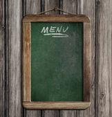 Aged green menu blackboard hanging on wooden wall — Stock Photo
