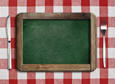Menu blackboard lying on table with knife and fork — Stock Photo