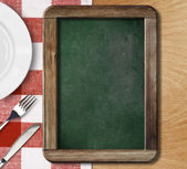 Menu blackboard lying on table with plate, knife and fork — 图库照片