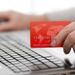 Man holding credit card in hand and entering security code using — Stock Photo