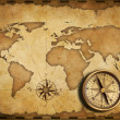 Aged brass antique nautical pocket compass with old map — Stock Photo