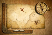 Aged treasure map, ruler and old brass compass on wooden table t — Stock Photo