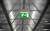 Green emergency exit sign in public building — Stock Photo