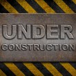 """under construction"" metal plate over hazard stripes — Stock Photo"