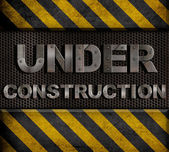 """""""under construction"""" metal text with rivets over grid — Zdjęcie stockowe"""