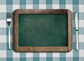 Menu blackboard lying on tablecloth with knife and fork — Stock Photo